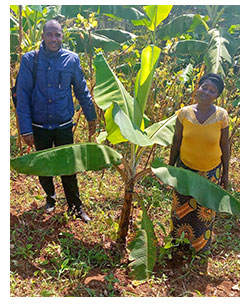 Jean Paul and a widow standing next to a banana tree