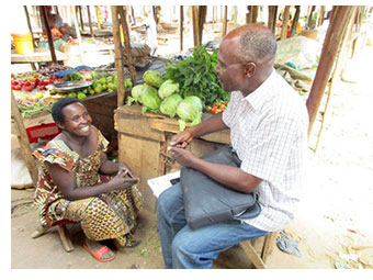 Esther at her vegetable stall with Francois Nitunga