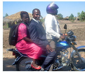 Pastor Evance and his wife Elisa on a motorbike taxi.