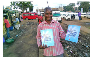 Pastor Evance with copies of Essentials of an Excellent Christian Marriage